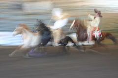 Mexican Rodeo Horse Race. Two mexican vaqueros chase another horse. Image blurred by subject movement at high speed royalty free stock image