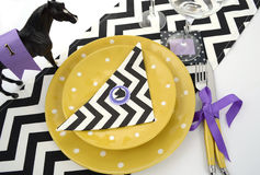 Horse racing carnival event luncheon table place setting. In purple, yellow theme, and black and white chevron strip table runner, overhead Royalty Free Stock Image