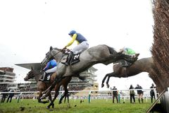 Horse Racing. Guitar pete 1st blue-yellow seen here jumping the last on the first cuircuit at cheltenham races 16-12-17 Stock Photography
