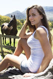 Horse racing time. Caucasian female sitting next to a horse meadow outside with horses in the background Stock Photo