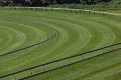 Horse Racing Track Corner. Green Grass horse racing track at the guard corner railing onto straight Royalty Free Stock Photo