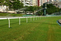 Horse racing track with sprinkler Stock Photos