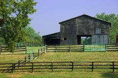 Horse Ranch Barn. An old rustic barn for horses sits at the back of a fenced ranch in Kentucky, USA stock photography