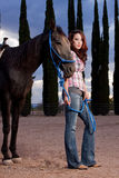 The horse and rider. A beautiful woman stands in the paddock with her horse Stock Photo