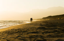 Horse rider couple at sunset beach, next to the sea Royalty Free Stock Images