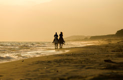 Horse rider couple at sunset beach, next to the sea Stock Image