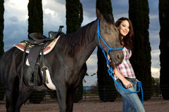 The horse and rider laughing together. A beautiful woman stands in the paddock with her horse. They're both very happy in this fun image stock images