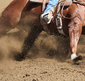 A horse and rider moving fast with dirt flying. A close up of a horse galloping and skidding with dirt flying Stock Photography