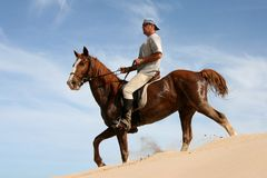 Horse rider on sand dune. Brown horse and rider on a sand dune against blue sky Royalty Free Stock Images