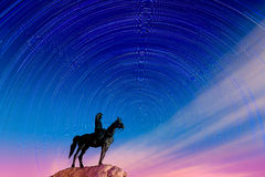 Horse rider statue looking at star-trails Royalty Free Stock Images