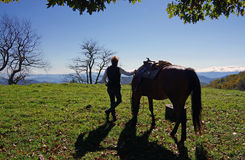 Horse and rider. A horse and rider taking a break while admiring a mountain vista royalty free stock photo