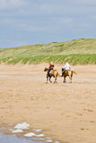 Horse riders on beach. Two girls riding horses on a beach Royalty Free Stock Image