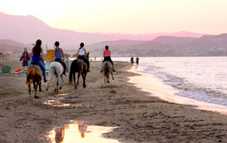 Horse riders on the beach. During sunset in Crete in Greece Stock Photos