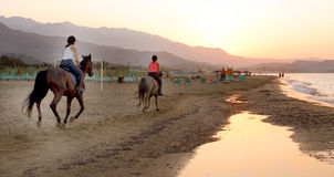 Horse riders on the beach. During sunset in Crete in Greece Stock Image