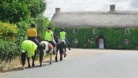 Horse riders. Building covered in ivy with group of people riding horses in a village of Withford, Devon Stock Photos