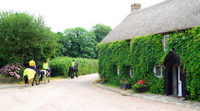 Horse riders. Building covered in ivy with group of people riding horses in a village of Withford, Devon Stock Images