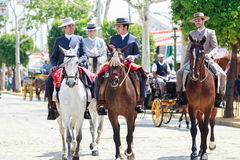 Horse riders taking a walk by the fair of Seville Royalty Free Stock Photos