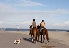 Horse riding. Two women on a horseback going for a ride on the beach royalty free stock photo