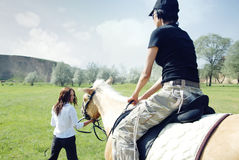 Horse riding. Lady riding on the horse with her trainer outdoors. Natural light and colors stock photos