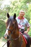 Horse Riding. A senior citizen enjoying horse riding activity at the countryside (focus on the horse Royalty Free Stock Photos