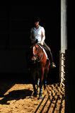 Horse Riding. Young woman riding horse in indoor arena Stock Photos