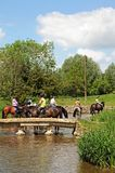 Horse riding along stream, Lower Slaughter. Stock Image