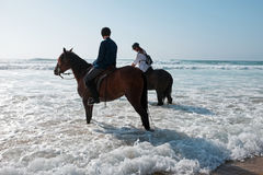 Horse riding at the beach at the ocean Royalty Free Stock Photos