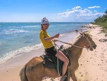Horse riding on the beach. Young tourist on horseback along the coast of Parque Nacional Del Este, East National Park, Dominican Republic. Horse riding is an Royalty Free Stock Photo