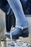 Horse riding boot in stirrup. Horse riders boot in stirrup, with blue jodhpurs. Some tack detail visible Stock Photo