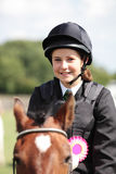 Horse riding competition. A teenager happy to have won a rosette horse riding Royalty Free Stock Photo