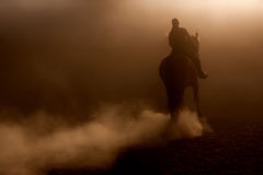 Horse riding in the dust Stock Images