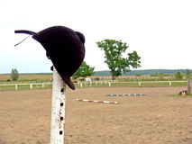 Horse riding item. A horse riding accessory hanging on a metal pole. Paddock and grassing horses in the background Royalty Free Stock Photography