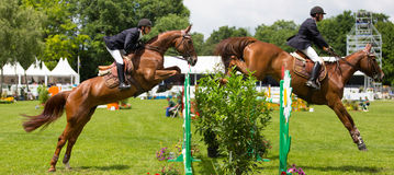 Equestrian riding event. Competitors jumping over fences at Jumping de Franconville equestrian event in France stock photography