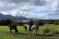 Horse Riding In Killarney National Park, County Kerry, Ireland. Bright sunshine and cloudy skies greet Horse riders at Killarney National Park. County Kerry Royalty Free Stock Image