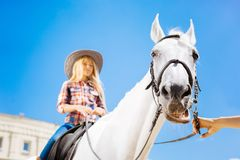 Blonde-haired teenage girl enjoying her horse riding lesson royalty free stock photography