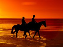 Horse riding at sunset. Horse riding by couple at dusk Royalty Free Stock Photos