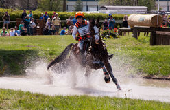 Horse running through water in a cross country race. Lexington, Kentucky - April 26, 2014: Sharon White riding Wundermaske at the 2014 Rolex Three-Day Event at Stock Photography
