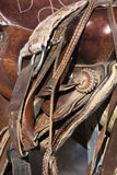 Horse Saddle on a Rail. Detail of a western style horse saddle and cinch on a rail. Vertical shot Royalty Free Stock Images
