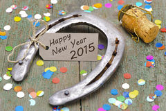 Horse shoe as talisman for new year 2015. Horse shoe with cork of champagne as talisman for new year 2015 Royalty Free Stock Images