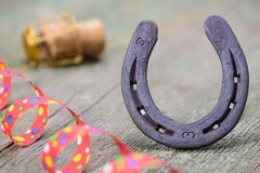 Horse shoe as talisman for new year. Horse shoe and cork of champagne as talisman for new year Stock Image
