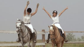Horse show jumping competition of two girls stock video