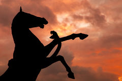 Horse and Snake monument silhouette with over cloudy red sky Royalty Free Stock Photography