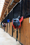 Horse stable. Inside of a horse stable with many rooms for horses and a close up of a saddle Stock Photo