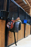 Horse stable. Inside of a horse stable with many rooms for horses and a close up of a saddle Royalty Free Stock Photography