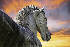 Horse sunrise. A marble horse statue with dramatic orange and red sunrise in background Royalty Free Stock Photo