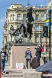 The Horse Tamer statue on Anichkov bridge and the people about it at a clear spring day. Stock Image