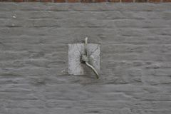 Horse tiebar in brick wall painted grey stock image