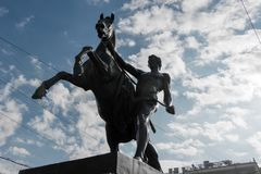Horse walking with a young man. RUSSIA, SAINT PETERSBURG - AUGUST 18, 2017: Famous sculpture `Horse walking with a young man` on Anichkov Bridge across the Stock Photo