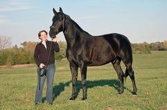 Horse and woman. Black Hanovarian horse and woman Royalty Free Stock Image