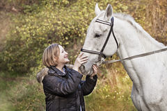 Horse. The woman on a glade irons a white horse Stock Images